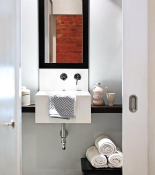 Phòng tắm với lựa chọn gam màu trắng xanh, giá đề đồ đặt dưới bồn nước